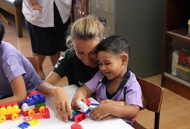 A volunteer and child play with building blocks in Thailand.