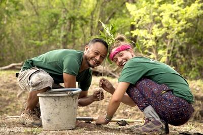 A Projects Abroad staff member and volunteer plant a tree sapling together at the Conservation Project in Costa Rica.