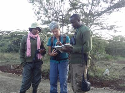 Projects Abroad staff and volunteers discuss information from a book used to identify bird species in Kenya.