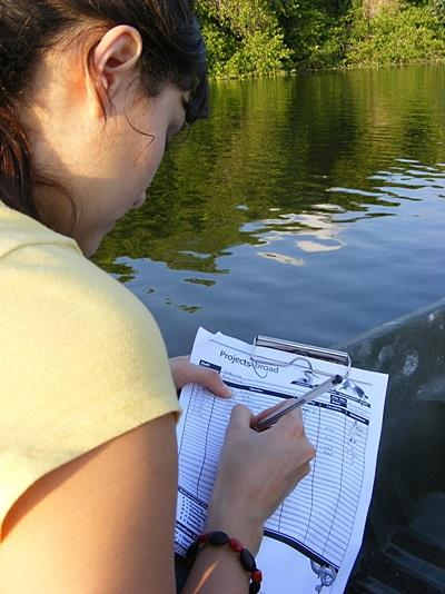 A Projects Abroad Conservation volunteer records data and numbers during a survey at a lagoon in Mexico.