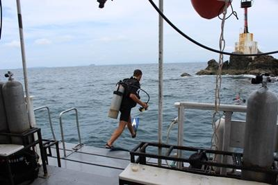 A Projects Abroad Conservation volunteer jumps into the water to begin a dive in Thailand.