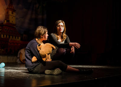 Two Romanian students appear on stage performing a play directed by a Projects Abroad volunteer.