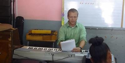 A volunteer at the Projects Abroad Music Project in Jamaica teaches piano to local children.