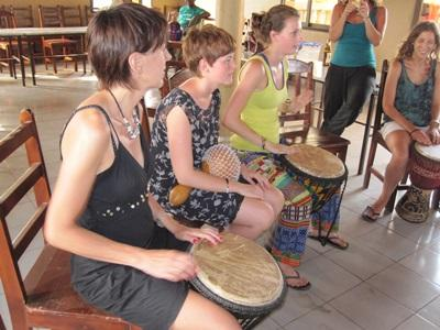 A group of Projects Abroad volunteers learn traditional drumming at their project in Togo.