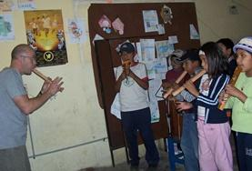 A volunteer on the Bolivia Creative & Performing Arts Projects teaches a child how to play a musical instrument.