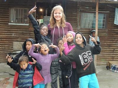 A group of local children spend time with a Projects Abroad volunteer in a South African township.