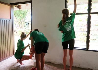 A group of Projects Abroad volunteers help paint a building in the local community in Fiji.