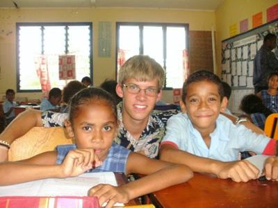 A Projects Abroad volunteer helps children with an activity in a school in Fiji.