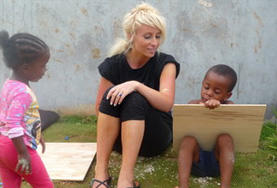 Volunteer on the Maroon Culture & Community project in Jamaica paints with local child