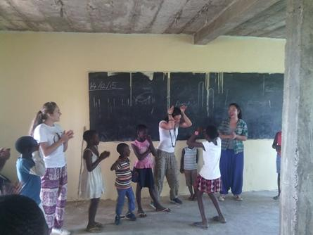Projects Abroad volunteers play and sing during a class with Ghanaian children in Africa.