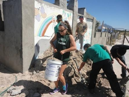 Projects Abroad Building volunteer fetches sand for construction in South Africa.