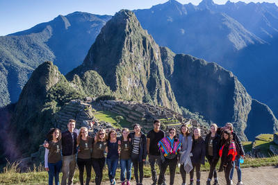 A group of volunteers overlooking Machu Picchu on a sunny day in Peru