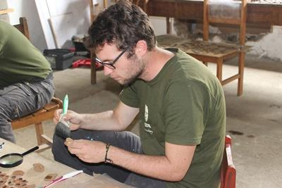 A volunteer on the High School Special Inca Project in Peru examines ceramic found on-site.