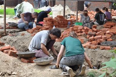 Teenage volunteers help rebuild a classroom destroyed by an earthquake at their Building Project in Nepal, Asia.