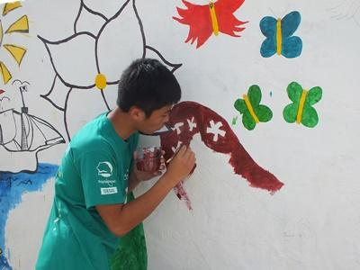 A wall at a kindergarten gets a new mural painted by Projects Abroad High School Special volunteers in Senegal.