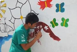 A High School Special volunteer on the Building & French Project in Senegal paints a mural at his placement.