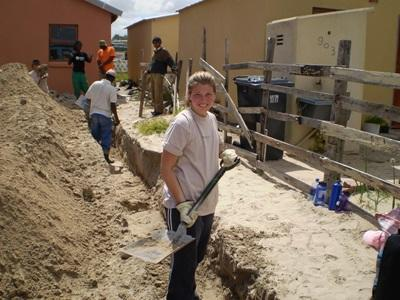 A teenage Projects Abroad volunteer helps dig the foundation for a new building in a township in Cape Town, South Africa.