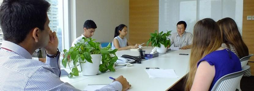 High school students interning abroad with Projects Abroad attend a meeting with local staff at a law firm in China.
