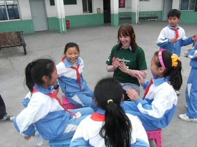 A high school student volunteering in China plays with students outdoors at a kindergarten.