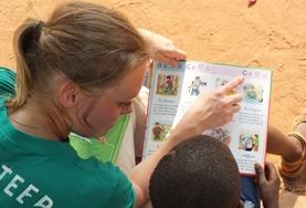 A High School Special volunteer reads to a young boy in Togo during her Care & Community with French Project.