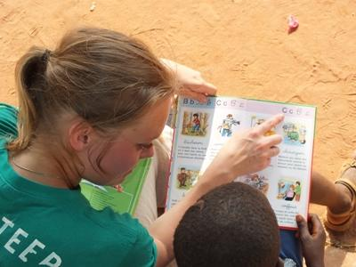 Projects Abroad High School Special volunteer reads aloud with a Togolese child at a care centre in Lomé.