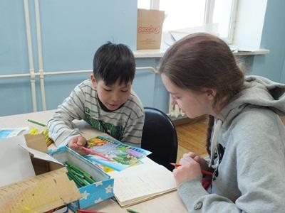 A High School Special volunteer helps a child with an activity in the classroom at the Projects Abroad Care & Community Project in Mongolia.