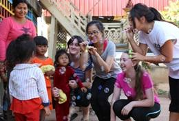 High School Special students on their Care & Community Project in Cambodia play a game with young children.