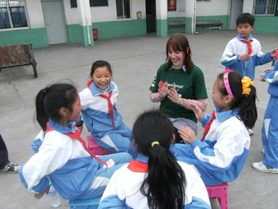 A teenage volunteers plays a game with children outside the classrrom during recess at her Care & Community High School Special placement.