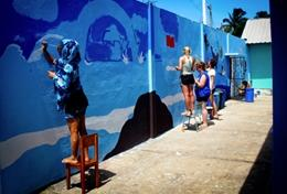 High School Special volunteers in Ecuador paint a school wall as part of their Care & Community Project.