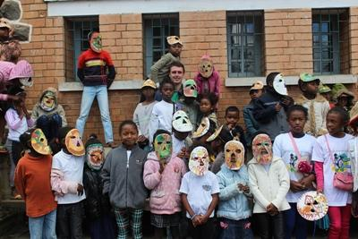 Projects Abroad volunteer with a group of local children and their masks created during an arts and crafts lesson in Madagascar.