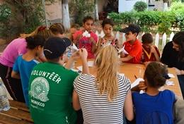 High School Special volunteers in Morocco work on an arts and crafts project with young children.
