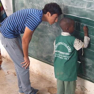 A high school student volunteering in Senegal helps a young boy with classwork on his Care & Community Project.