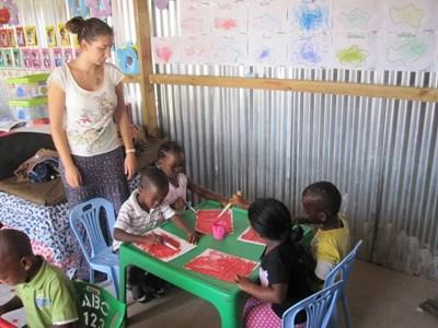 A Projects Abroad volunteer helps children with an arts & crafts activity at a day care centre in Cape Town, South Africa.