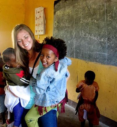 A high school student volunteering with Projects Abroad in Tanzania holds children at her Care & Community Project.