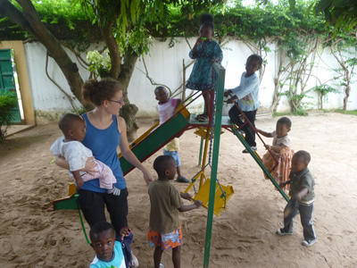 A teenage volunteer plays on the playground with children at her Projects Abroad Care & Community Project in Togo.