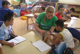 Care & Community High School Special volunteers in Vietnam talk to children during an activity in class.