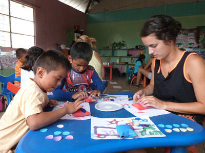 Two local children participate in a creative activity with a Projects Abroad volunteer at a care centre in Ecuador.