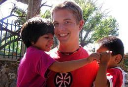 A High School Special Care & Spanish volunteer plays with children on the playground.