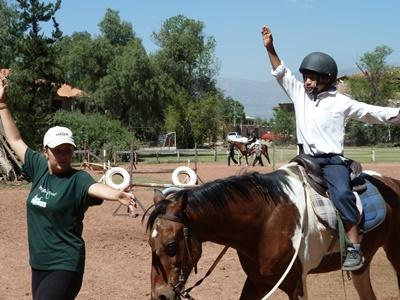 A Bolivian child participates in a therapy session with a Projects Abroad Equine Therapy volunteer in Cochabamba.