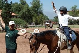 An Equine Therapy & Community student volunteer on the High School Special helps a young boy gain confidence on a horse.