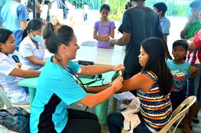 A teenage volunteer conducts a health check in the Philippines, Southeast Asia.