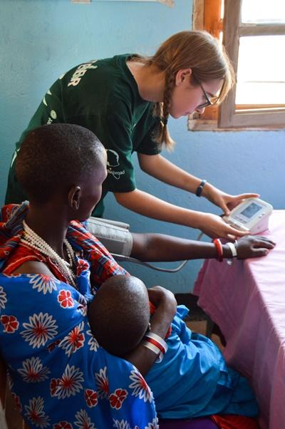 Projects Abroad Public Health volunteer assists with taking blood pressure readings at an outreach in Tanzania, Africa.