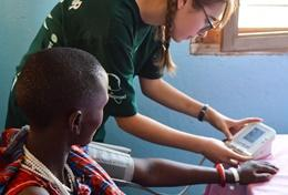 Volunteers on the Public Health High School Special in Tanzania listen to the advice of a local doctor before a medical outreach.