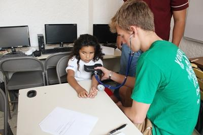 A Mexican child gets her blood pressure checked by a Projects Abroad volunteer during an outreach at the Public Health High School Special.