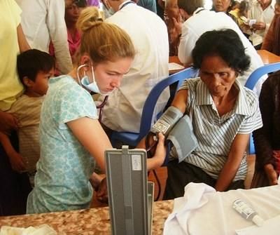 A Public Health volunteer at the Projects Abroad High School Special measures blood pressure during a medical outreach in Cambodia.