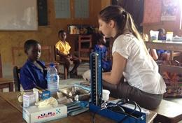 A Medicine High School Special volunteer checks a young boy's vital signs in Ghana.