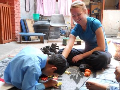A Nepalese child works on a puzzle activity with the help of a volunteer