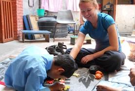 A student on the Physiotherapy High School Special in Nepal works with a young boy at her placement.