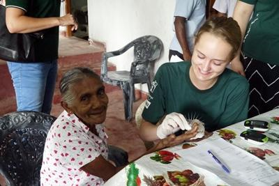 A Projects Abroad High School Special volunteer helps check blood sugar levels during a medical outreach in Sri Lanka.