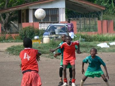 A Projects Abroad volunteer on the High School Special teaches soccer skills to children in Ghana.